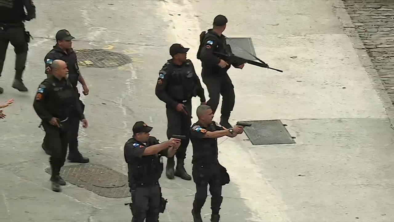 Policiais apontam armas para torcedores que arremessam pedras contra os militares